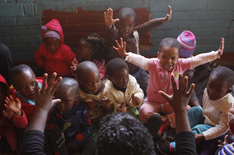In this photo taken Tuesday May 21, 2013 children learn to count to ten at a play center at the Dube hostel in Soweto South Africa. The center is provided with educational toys from Cotlands, a local non-profit organization that promotes early learning opportunities for children. Cotlands first opened it's doors 77 years ago offering adoption services for abandoned babies. In 1996 it opened an HIV hospice to address the increased HIV birth rate which claimed 98 children in 2002. In the past three years no child has died leading to the closure of the HIV hospice and now prioritizes it's efforts into advocation for an improvement in early childhood education. (AP Photo/Denis Farrell)