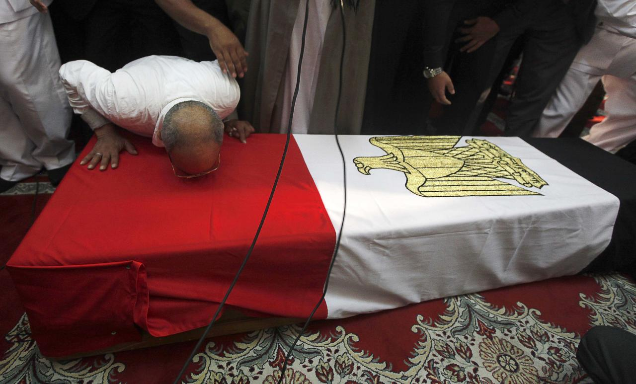 A mourner kisses the coffin of Police General Nabil Farag, who was killed during Thursday's security operation in Kerdasa, during his funeral service at Al-Rashdan Mosque in Cairo's Nasr City district September 20, 2013. Egyptian security forces were hunting for supporters of deposed President Mohamed Mursi of the Muslim Brotherhood on Friday after retaking control of a town near Cairo in a crackdown on Islamists. On Thursday, army and police forces stormed Kerdasa where Islamist sympathies run deep and hostility to the authorities has grown since the army overthrew and imprisoned Mursi on July 3. REUTERS/Mohamed Abd El Ghany (EGYPT - Tags: POLITICS CIVIL UNREST MILITARY OBITUARY)