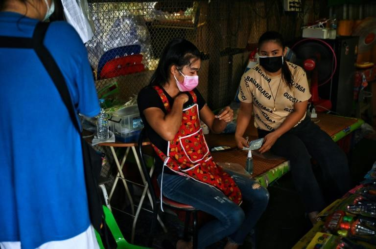 Vendors take sweat-covered testing swabs from under their clothing (AFP/Lillian SUWANRUMPHA)