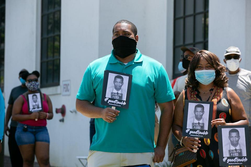 "<p>Mourners looked on as Lewis arrived in Montgomery, Alabama. Individuals wore masks in order to protect themselves and other from COVID-19. They also carried signs with Lewis's iconic police mugshot depicted on the front. In 2014, Lewis <a href=""https://www.nbcnews.com/news/us-news/rep-john-lewis-tweets-his-mugshot-educate-inform-n150261"" rel=""nofollow noopener"" target=""_blank"" data-ylk=""slk:tweeted"" class=""link rapid-noclick-resp"">tweeted</a> this photograph to educate his followers about the history of racism in the United States. The caption read, ""53 yrs ago today I was released from Parchman Penitentiary after being arrested in Jackson for using the 'white' restroom.""<br></p>"