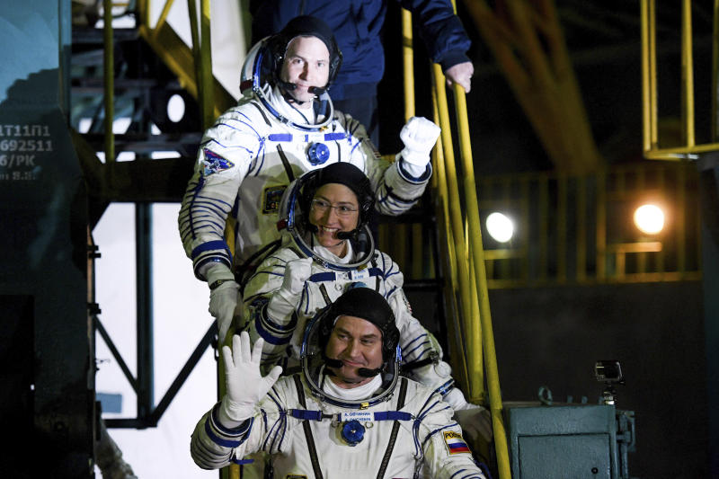 U.S. astronauts Christina Hammock Koch, centre, Nick Hague, above, and Russian cosmonaut Alexey Ovchinin, crew members of the mission to the International Space Station, ISS, wave as they board to the rocket prior the launch of Soyuz-FG rocket at the Russian leased Baikonur cosmodrome, Kazakhstan, Thursday, March 14, 2019. (AP Photo/Kyrill Kudryavtsev, Pool)