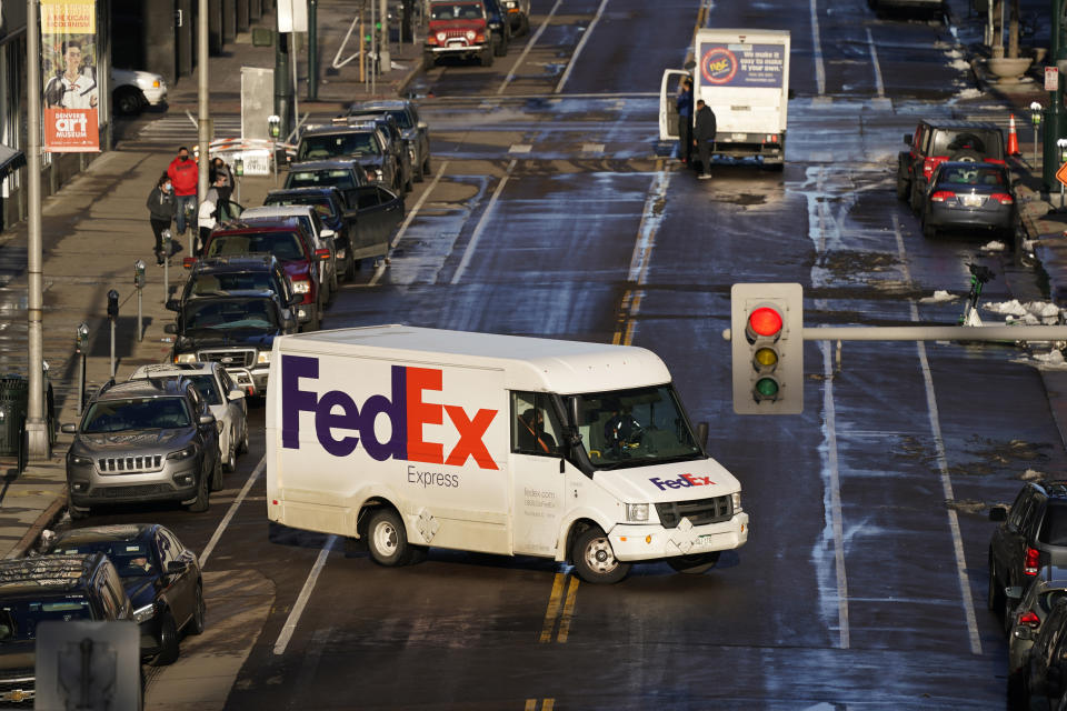 A FedEx delivery vehicle makes a U-turn near the Denver Pavilions Tuesday, Dec. 29, 2020, in downtown Denver. (AP Photo/David Zalubowski)