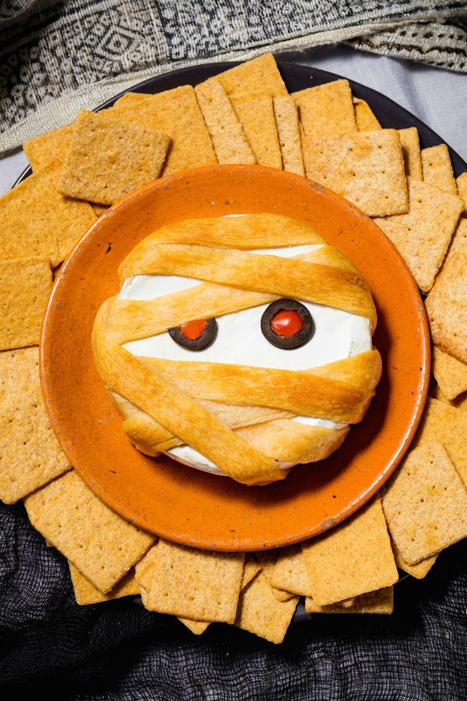 """<p>Thanks to puff pastry, your basic baked brie becomes a totally spooky Halloween appetizer.</p><p>Get the recipe from <a href=""""https://www.delish.com/holiday-recipes/halloween/recipes/a49347/mummy-brie-recipe/"""" rel=""""nofollow noopener"""" target=""""_blank"""" data-ylk=""""slk:Delish"""" class=""""link rapid-noclick-resp"""">Delish</a>.</p>"""
