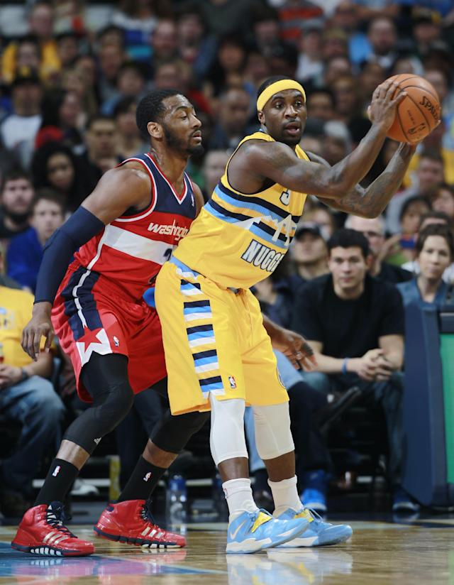 Washington Wizards guard John Wall, left, pressures Denver Nuggets guard Ty Lawson in the first quarter of an NBA basketball game, Sunday, March 23, 2014, in Denver. (AP Photo/David Zalubowski)