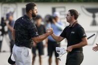 Jon Rahm of Spain, left, shakes hands with Patrick Cantlay on the 18th green during the third round of the Tour Championship golf tournament Saturday, Sept. 4, 2021, at East Lake Golf Club in Atlanta. (AP Photo/Brynn Anderson)