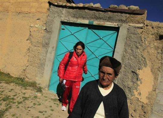Marathon runner Gladys Tejeda, the first Peruvian athlete who qualified for the 2012 London Olympic Games, accompanied by her mother Marcelina Pucuhuaranga (R), leaves her home to go for training in the Andean province of Junin, May 14, 2012.