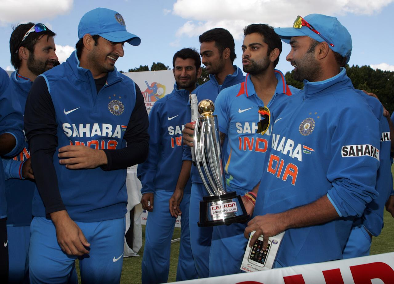 India players celebrate with the Celkon Trophy after winning the final game of the 5 match cricket ODI series between hosts Zimbabwe and India at Queens Sports Club in Harare on August 3, 2013. AFP PHOTO /Jekesai Njikizana.        (Photo credit should read JEKESAI NJIKIZANA/AFP/Getty Images)