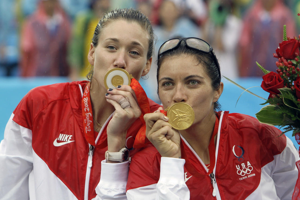 FILE - This Aug. 21, 2008, file photo shows Misty May-Treanor, right, and Kerri Walsh, of the United States, kssing their gold medals during the medal ceremony for women's beach volleyball at the Beijing 2008 Olympics in Beijing. No one will be more in the spotlight than Walsh and May-Treanor, who won gold medals in Athens and Beijing and are favorites for a third title in London. (AP Photo/Natacha Pisarenko, File)