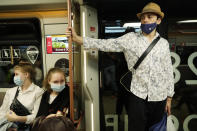 People wearing face masks travel on a metro train in Moscow, Russia, Friday, July 2, 2021. Russian authorities have reported a record-breaking 679 new coronavirus deaths, a fourth day in a row with the highest daily death toll in the pandemic, yet the Kremlin has insisted that no plans for another lockdown are being discussed. (AP Photo/Pavel Golovkin)