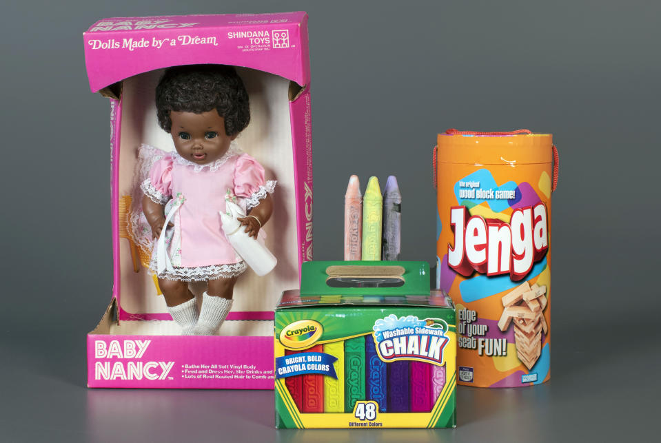 This photo, provided by the National Toy Hall of Fame, shows Baby Nancy, by Shindana Toys; Sidewalk Chalk, by Crayola; and Jenga, by Parker Brothers, left to right, that were inducted into the National Toy Hall of Fame on Thursday, Nov, 5, 2020. The honorees were chosen by a panel of experts from among 12 finalists and will be on permanent display inside The Strong National Museum of Play, in Rochester, New York. (Victoria Gray/National Toy Hall of Fame via AP)