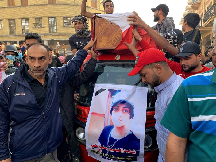 Mourners and protesters escort the flag-draped coffin of Munir Ali, seen in poster, whose family said was killed during anti-government demonstrations, during his funeral in Baghdad, Iraq, Sunday, Nov. 24, 2019. (AP Photo/Ali Abdul Hassan)