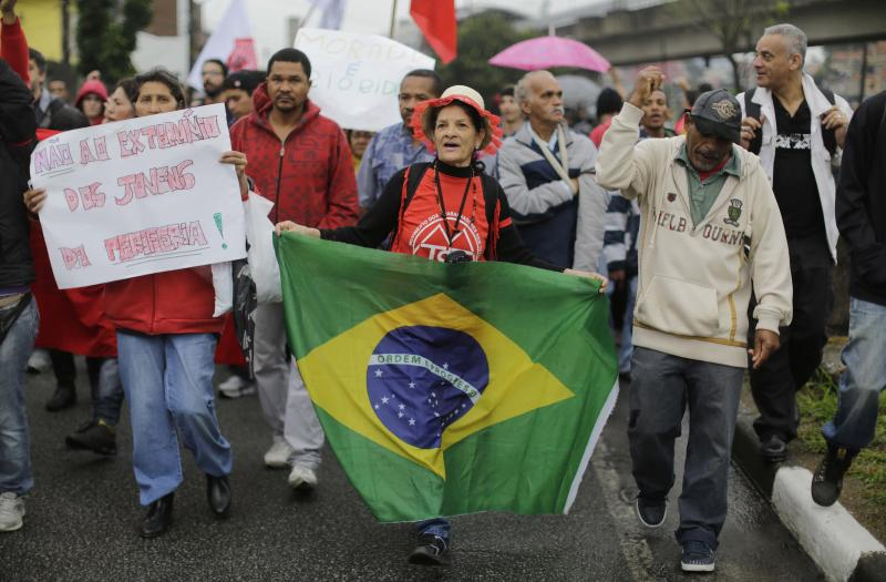"""People a protest in the Capao Redondo neighborhood of Sao Paulo, Brazil, Tuesday, June 25, 2013. Protesters on Tuesday returned to the streets in low-income suburbs of Brazil's biggest city to demand better education, transport and health services, one day after President Dilma Rousseff proposed a wide range of actions to reform Brazil's political system and services. The sign at left reads in Portuguese """"No to the extermination of youth on the periphery!,"""" referring to the poor outskirts of the city. (AP Photo/Nelson Antoine)"""