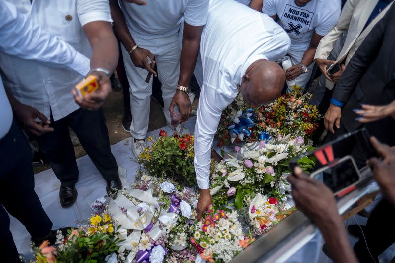 People place flowers at a memorial outside the Presidential Palace in memory of President Jovenel Moise