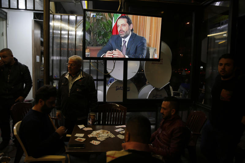 """Lebanese smoke water pipes and play cards at a coffee shop as they listen to outgoing Lebanese Prime Minister Saad Hariri during a live interview shown on his Future TV from Saudi Arabia in Beirut, Lebanon, Sunday, Nov. 12, 2017. Hariri said Sunday he will return to his country """"very soon"""" amid a political crisis that erupted when he announced his sudden resignation on Nov. 4 in Saudi Arabia. (AP Photo/Hassan Ammar)"""