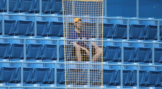 A fan of the Blue Jays watches from behind the loosely hanging mesh rectangles that pass as foul poles in Toronto. (Tom Szczerbowski/Getty Images)