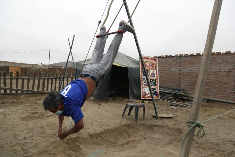 """Circus clown Santos Chiroque, whose performance name is """"Piojito,"""" or Little Tick, trains on a self-made swing outside his home on the outskirts of Lima, Peru, Monday, Aug. 10, 2020. Chiroque's family used to run their own small circus, but since March when the lockdown to curb COVID-19 closed their business, and the requirement for people over 60 to self-quarantine kept the 74-year-old at home, they started selling circus food like caramelized apples to survive. (AP Photo/Martin Mejia)"""