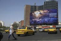 "In this Wednesday, May 29, 2019 photo, People walk and vehicles drive at Vali-e-Asr Square in downtown Tehran where an anti-Israeli billboard is place ahead of the Al-Quds, Jerusalem, Day, Iran. Mysterious attacks on oil tankers near the strategic Strait of Hormuz show how susceptible one of the world's crucial chokepoints for global energy supplies remains, 30 years after the U.S. Navy and Iran found themselves entangled a similarly shadowy conflict. The so-called ""Tanker War"" saw American naval ships escort reflagged Kuwaiti oil tankers through the Persian Gulf and the strait after Iranian mines damaged vessels in the region. It culminated in a one-day naval battle between Washington and Tehran, as well as saw America accidentally shoot down an Iranian passenger jet, killing 290 people. (AP Photo/Ebrahim Noroozi)"