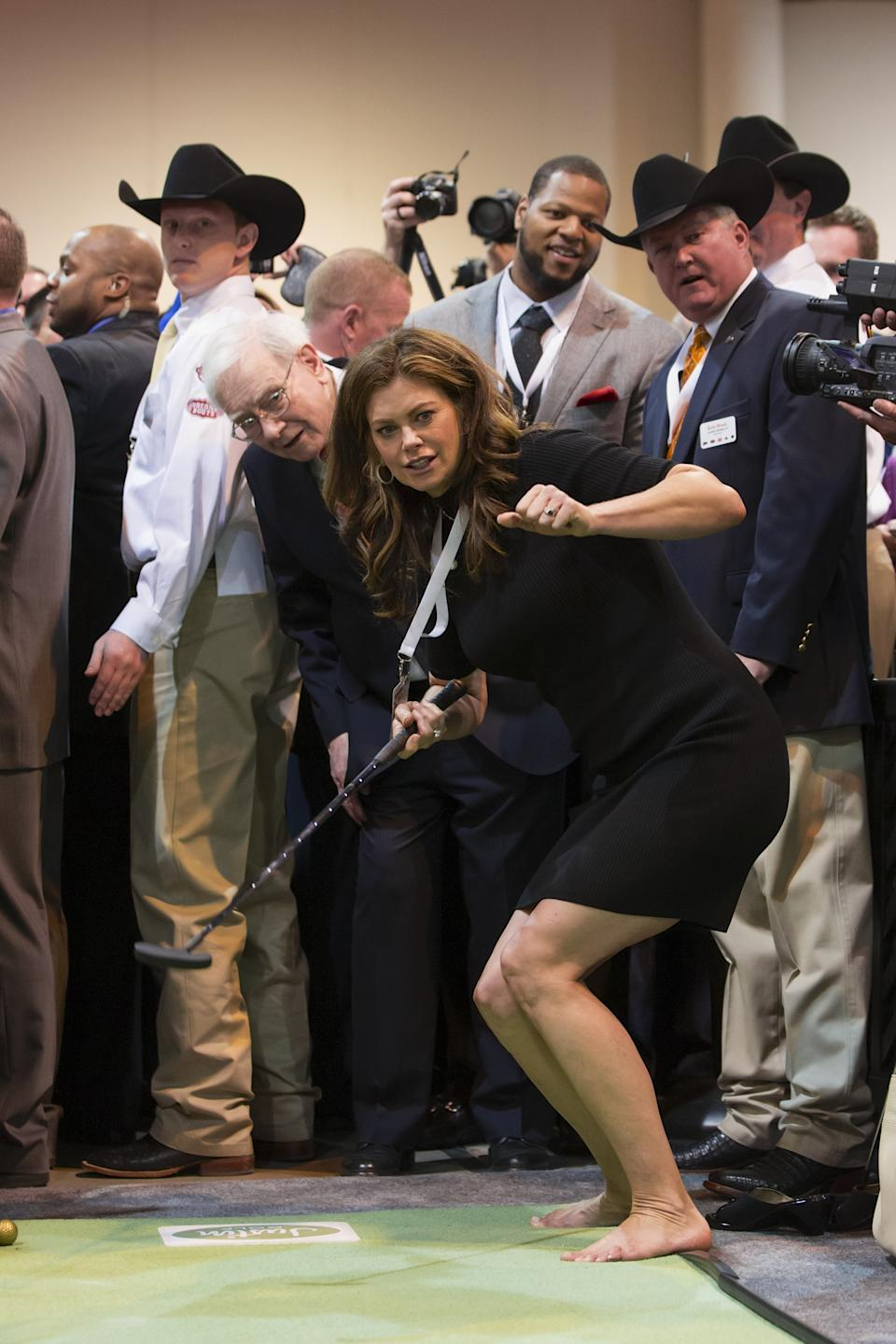 Former model and current businesswoman Kathy Ireland follows the path of her putt with Warren Buffett behind her, at the Justin Boots indoor mini golf lane in Omaha, Neb., Saturday, May 4, 2013, at the annual Berkshire Hathaway shareholder meeting. (AP Photo/Nati Harnik)