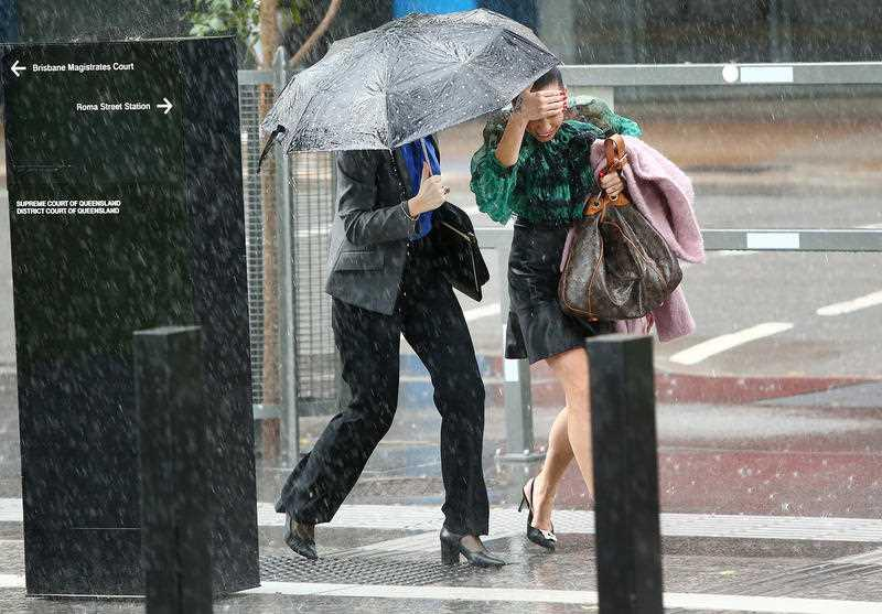 Pedestrians run through rain in the CBD, Brisbane.