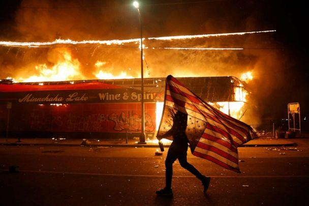 PHOTO: A protester carries the carries a U.S. flag upside, a sign of distress, next to a burning building Thursday, May 28, 2020, in Minneapolis. Protests over the death of George Floyd, a black man who died in police custody Monday. (Julio Cortez/AP)