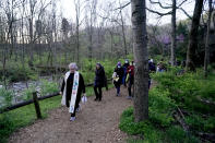 Rev. Beth Smith McCaw leads worshipers on a walk through the woods to their Easter Sunday sunrise service at Radnor Lake State Park Sunday, April 4, 2021, in Nashville, Tenn. Their annual sunrise service at the lake did not take place in 2020 because of COVID-19, but the church decided to reinstate it this year. (AP Photo/Mark Humphrey)