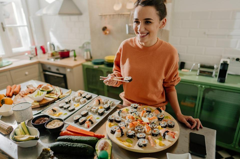 Photo of a smiling young woman holding a sushi roll with a pair of chopsticks by the kitchen counter.