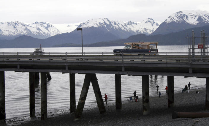 FILE - In this May 24, 2015, file photo, a vehicle drives on a pier to be loaded onto an Alaska state ferry while people fish underneath the pier in Homer, Alaska. The U.S. Supreme Court will hear oral arguments Monday, April 19, 2021, in a case that will determine who is eligible to receive more than $530 million in federal virus relief funding set aside for tribes more than a year ago. More than a dozen Native American tribes sued the U.S. Treasury Department to keep the money out of the hands of Alaska Native corporations, which provide services to Alaska Natives but do not have a government-to-government relationship with the United States. (AP Photo/Mark Thiessen, File)