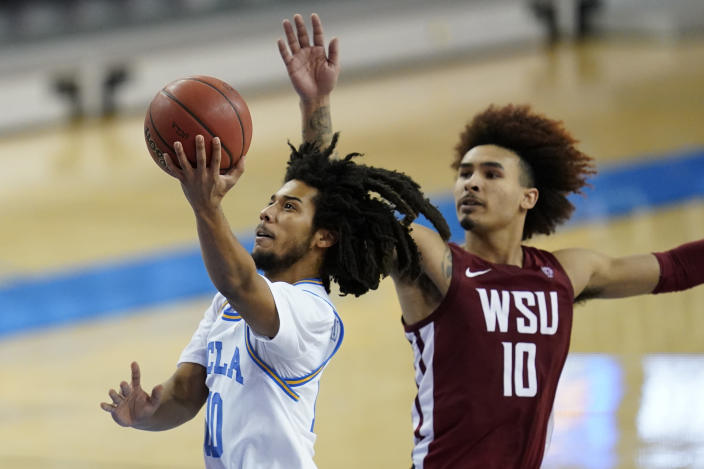 UCLA guard Tyger Campbell, left, shoots against Washington State guard Isaac Bonton, right, during the second half of an NCAA college basketball game Thursday, Jan. 14, 2021, in Los Angeles. (AP Photo/Ashley Landis)