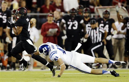 Stanford's Drew Terrell, left, runs past Duke punter Will Monday on his way to a 76-yard punt return for a touchdown during the first half of an NCAA college football game in Stanford, Calif., Saturday, Sept. 8, 2012. (AP Photo/Marcio Jose Sanchez)