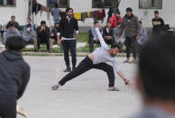 A man reaches to field the ball as migrants play a game of cricket in Blazuj migrant camp in Bosnia's capital of Sarajevo Wednesday, May 19, 2021. (AP Photo/Kemal Softic)
