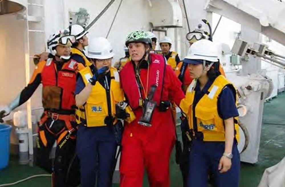 In this photo released by Japan Coast Guard, British adventurer Sarah Outen, second from right, is escorted by Japan coast guard personnel on board a patrol boat PLH-05 Zao after she was rescued in the Pacific Ocean off northeastern coast of Japan, Friday, June 8, 2012. Outen's blog said she was hit by a storm during her attempted journey around the world, and that her boat rolled over and was damaged. Another Briton on a similar trek was still awaiting rescue. (AP Photo/Japan Coast Guard)