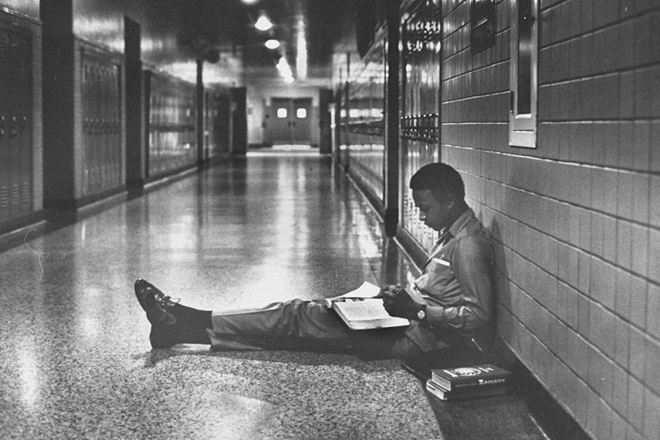 <p>A high school student attempts to get some studying done while sitting in an empty hallway. </p>