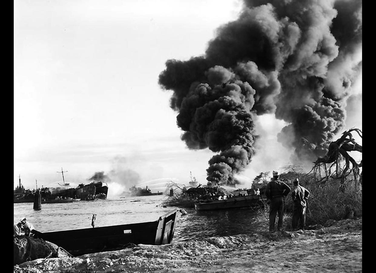 Smoke rises from the wreck of USS LST-480, at right, as tugs and other craft try to put out her fires in Pearl Harbor, Hawaii's West Loch area.