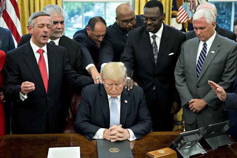 President Trump bows his head during a prayer while surrounded by U.S. Vice President Mike Pence, faith leaders and evangelical ministers after signing a proclamation declaring a day of prayer in the Oval Office of the White House in Washington, D.C., U.S., on Friday, Sept. 1, 2017. (Bloomberg via Getty Images)