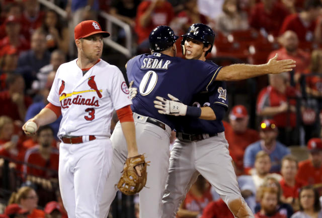 Milwaukee Brewers' Christian Yelich, right, gets a hug from third base coach Ed Sedar (0) after hitting a three-run triple as St. Louis Cardinals third baseman Jedd Gyorko (3) walks past during the fourth inning of a baseball game Tuesday, Sept. 25, 2018, in St. Louis. (AP Photo/Jeff Roberson)
