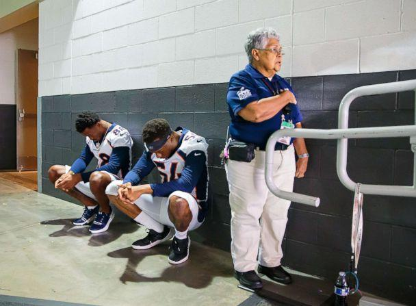 PHOTO: A stadium security guard stands with her hand over her heart as Denver Broncos linebacker Brandon Marshall (54) and wide receiver Demaryius Thomas (88) sit in silent protest during the national anthem prior a game, Aug. 30, 2018 in Glendale, Ariz. (Mark J. Rebilas/USA TODAY Sports)