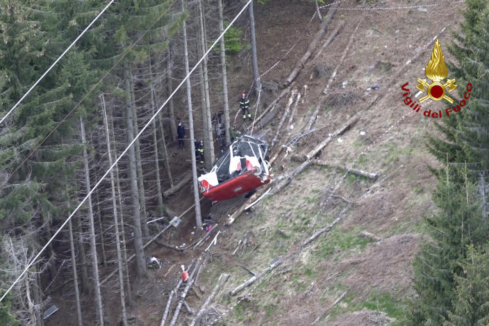 Rescuers work by the wreckage of a cable car after it collapsed near the summit of the Stresa-Mottarone line in the Piedmont region, northern Italy, as seen from the aerial photograph, Sunday, May 23, 2021. Italy's transport minister was heading Monday, May 24, 2021 to the scene of a cable car disaster that killed 14 people when the lead cable apparently snapped and the cabin careened back down the mountain until it pulled off the line and crashed to the ground. (Vigili del Fuoco Firefighters via AP)