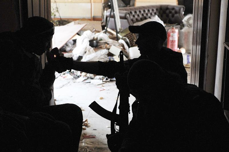 A pro-Russian separatist lights a feloow fighter's cigarette at Donetsk's Sergey Prokofiev international airport on October 16, 2014 (AFP Photo/Dominique Faget)