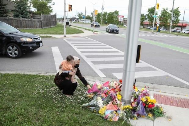 Nafisa Azima carries Seena Safdari while laying flowers at the crime scene where a man driving a pickup truck jumped the curb and ran over the Muslim family.