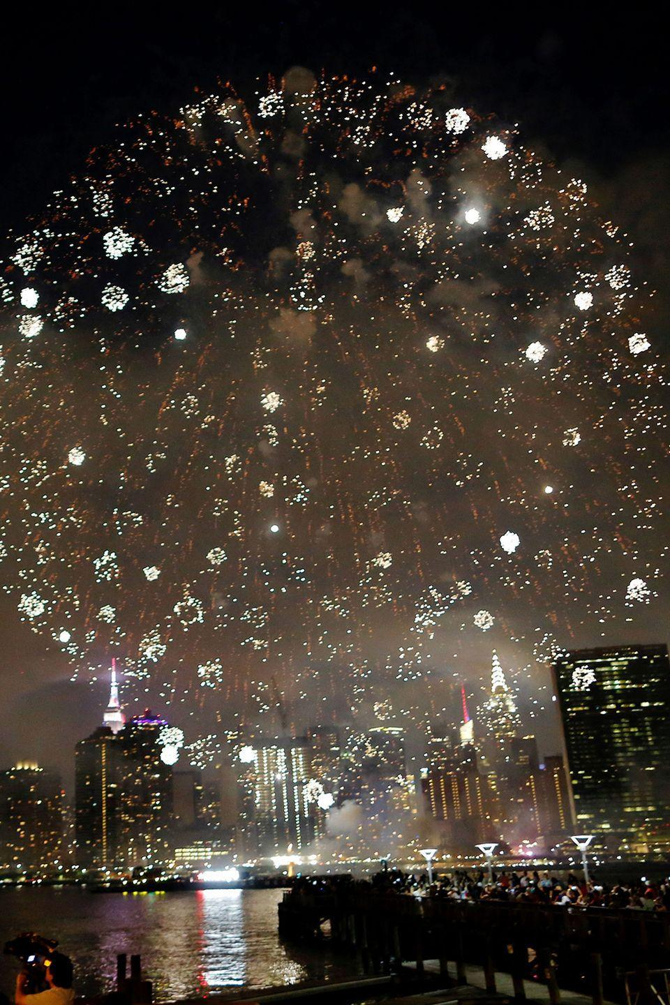 <p>People watch the annual Macy's 4th of July fireworks show from Queens, New York.</p>