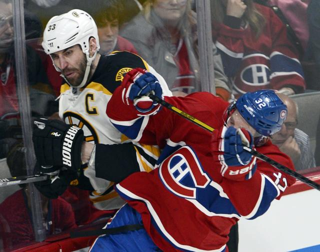 Boston Bruins defenseman Zdeno Chara (33) is checked by Montreal Canadiens left wing Travis Moen (32) during the third period in Game 4 in the second round of the NHL Stanley Cup playoffs Thursday, May 8, 2014, in Montreal. (AP Photo/The Canadian Press, Ryan Remiorz)