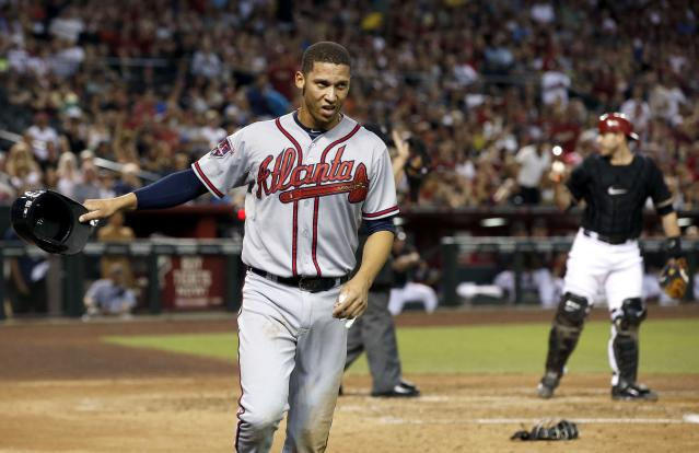 Atlanta Braves' Andrelton Simmons waves to a teammate with his helmet after he scored a run, as Arizona Diamondbacks' Miguel Montero, right, talks with the umpire about the call at home during the third inning of a baseball game Saturday, June 7, 2014, in Phoenix. (AP Photo/Ross D. Franklin)