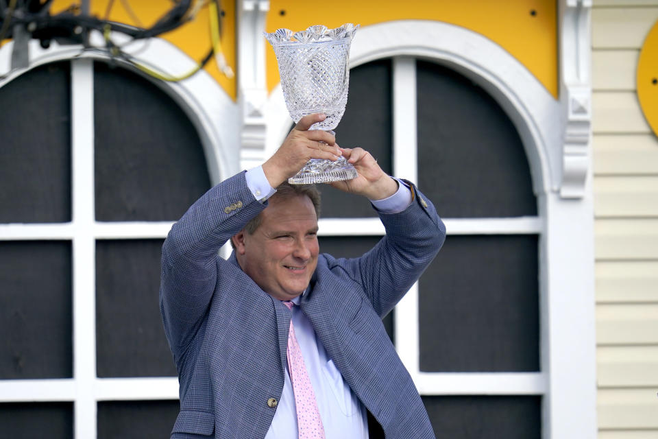 Trainer Michael Trainer Michael J. Maker holds a trophy after his horse, Army Wife, won the Black-Eyed Susan Stakes horse race at Pimlico Race Course, Friday, May 14, 2021, in Baltimore. (AP Photo/Julio Cortez)