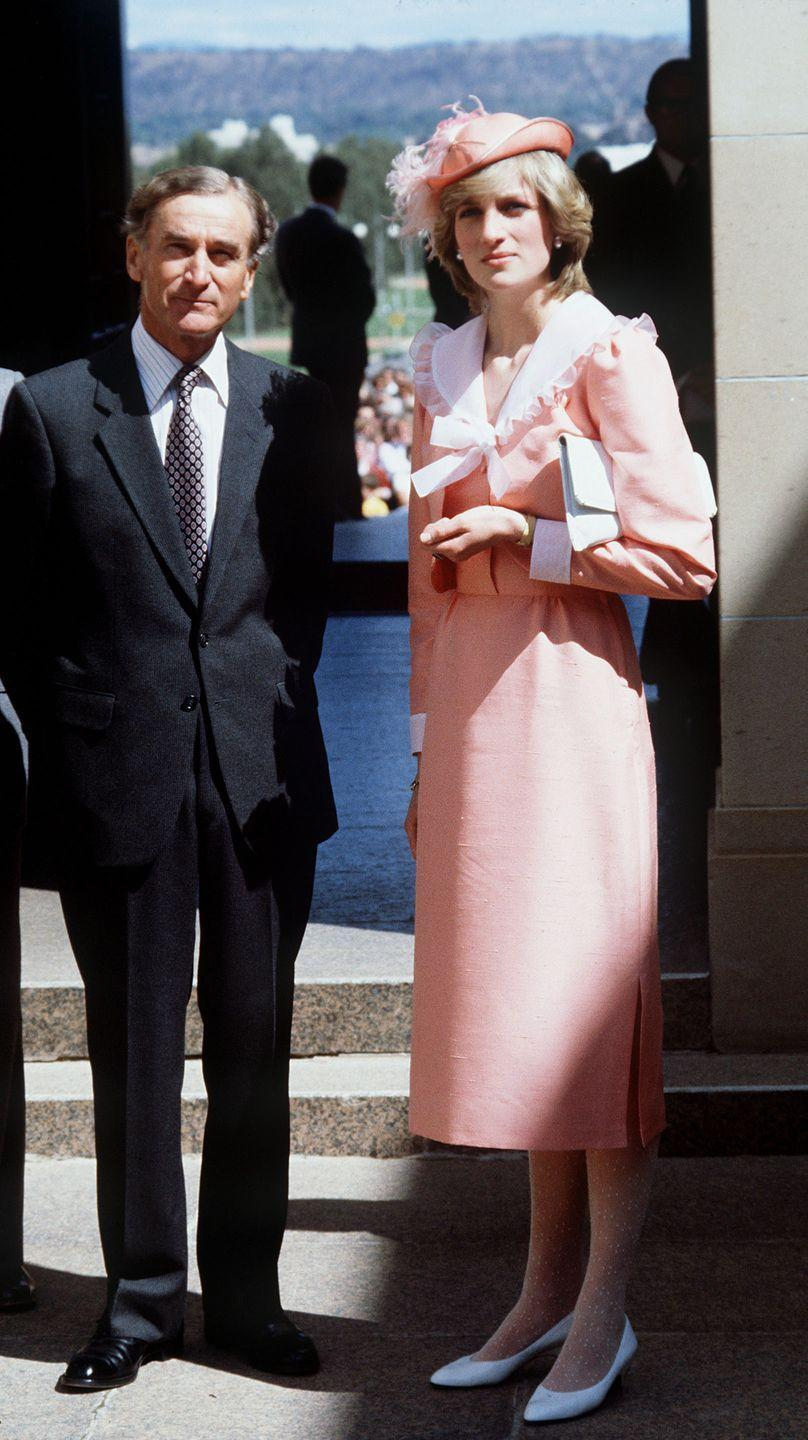 <p>In a pink dress and hat paired with white pumps while visiting a war memorial in Canberra, Australia. </p>