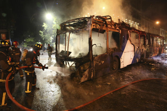 Firefighters put out the flames on a burning bus during a protest against the rising cost of subway and bus fares, in Santiago, Friday, Oct. 18, 2019. (Photo: Esteban Felix/AP)