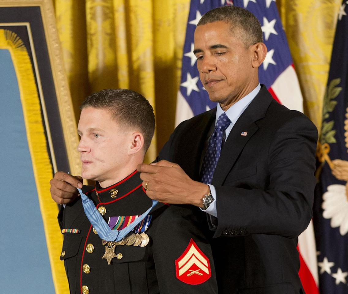 "President Barack Obama awards the Medal of Honor to retired Marine Cpl. William ""Kyle"" Carpenter, Thursday, June 19, 2014, in the East Room of the White House in Washington. Carpenter took a blow from a grenade to protect a fellow Marine in Afghanistan, sustaining major wounds including the loss of his right eye. He is the eighth living recipient to be chosen for the Medal of Honor for actions in Iraq or Afghanistan. (AP Photo/Pablo Martinez Monsivais)"