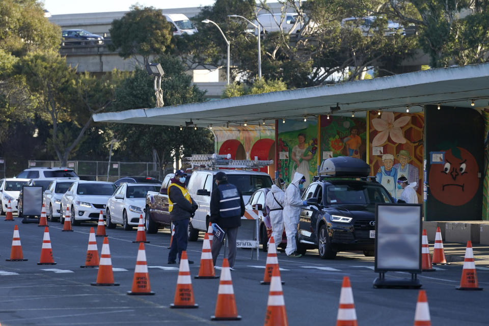 FILE - In this Dec. 22, 2020 file photo cars line up as healthcare workers ready COVID-19 tests at the CityTestSF at Alemany Farmer's Market location during the coronavirus pandemic in San Francisco. California became the first state to record 2 million confirmed coronavirus cases, reaching the milestone on Christmas Eve as close to the entire state was under a strict stay-at-home order and hospitals were flooded with the largest crush of cases since the pandemic began.(AP Photo/Jeff Chiu)