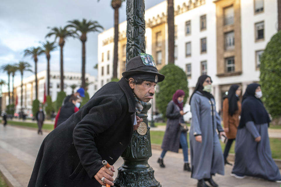Belhussein Abdelsalam, a Charlie Chaplin impersonator performs as people walk past in an avenue in Rabat, Morocco, Thursday, Dec. 17, 2020. When 58-year-old Moroccan Belhussein Abdelsalam was arrested and lost his job three decades ago, he saw Charlie Chaplin on television and in that moment decided upon a new career: impersonating the British actor and silent movie maker remembered for his Little Tramp character. (AP Photo/Mosa'ab Elshamy)
