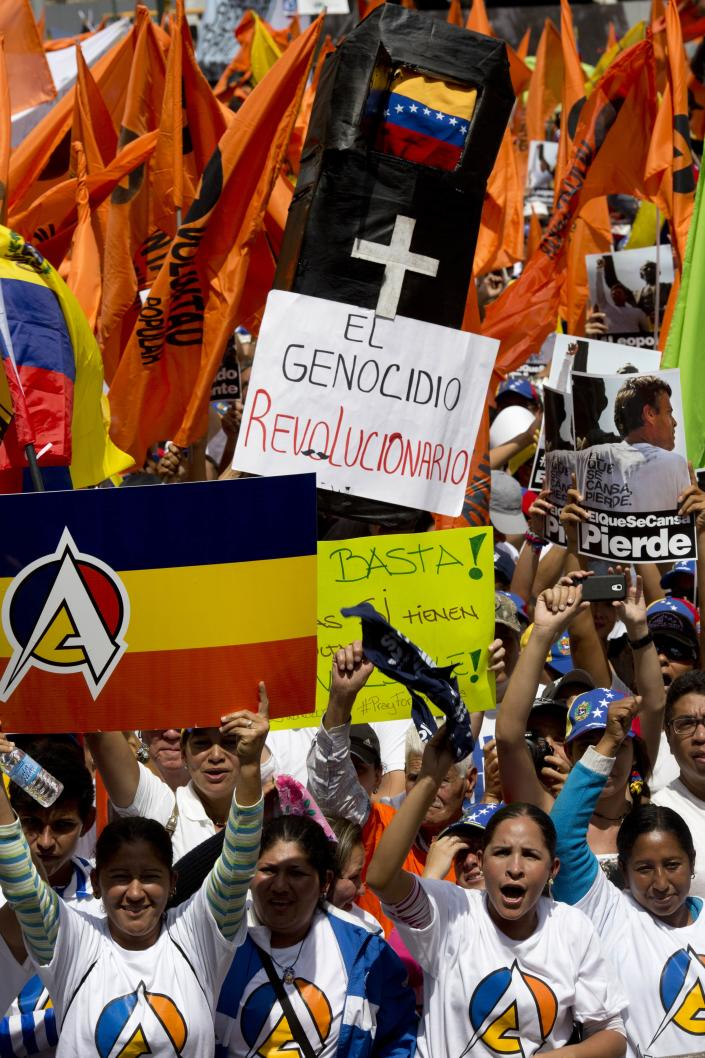 """Anti-government demonstrators participate in a rally in Caracas, Venezuela, Saturday, Feb. 22, 2014. Supporters and opponents of the government of President Nicolas Maduro are holding competing rallies in the bitterly divided country. The message on a mock coffin in the background reads in Spanish: """"The revolutionary genocide."""" (AP Photo/Rodrigo Abd)"""