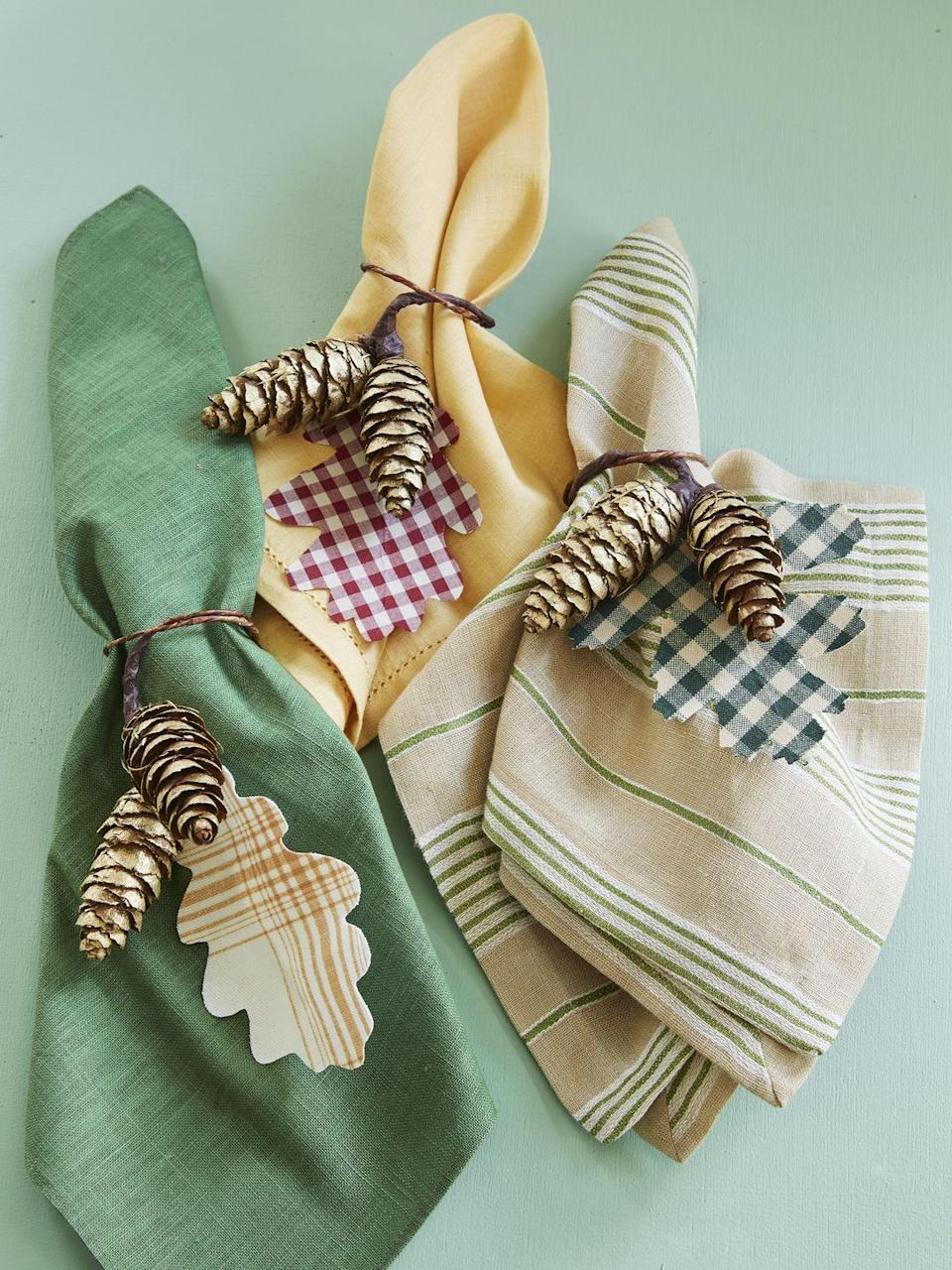 <p>Oak-shaped leaves cut from scraps of fabric get tied up with mini pine cones that have been spray painted gold. Tie around corresponding color napkins for an on-point table setting.</p>